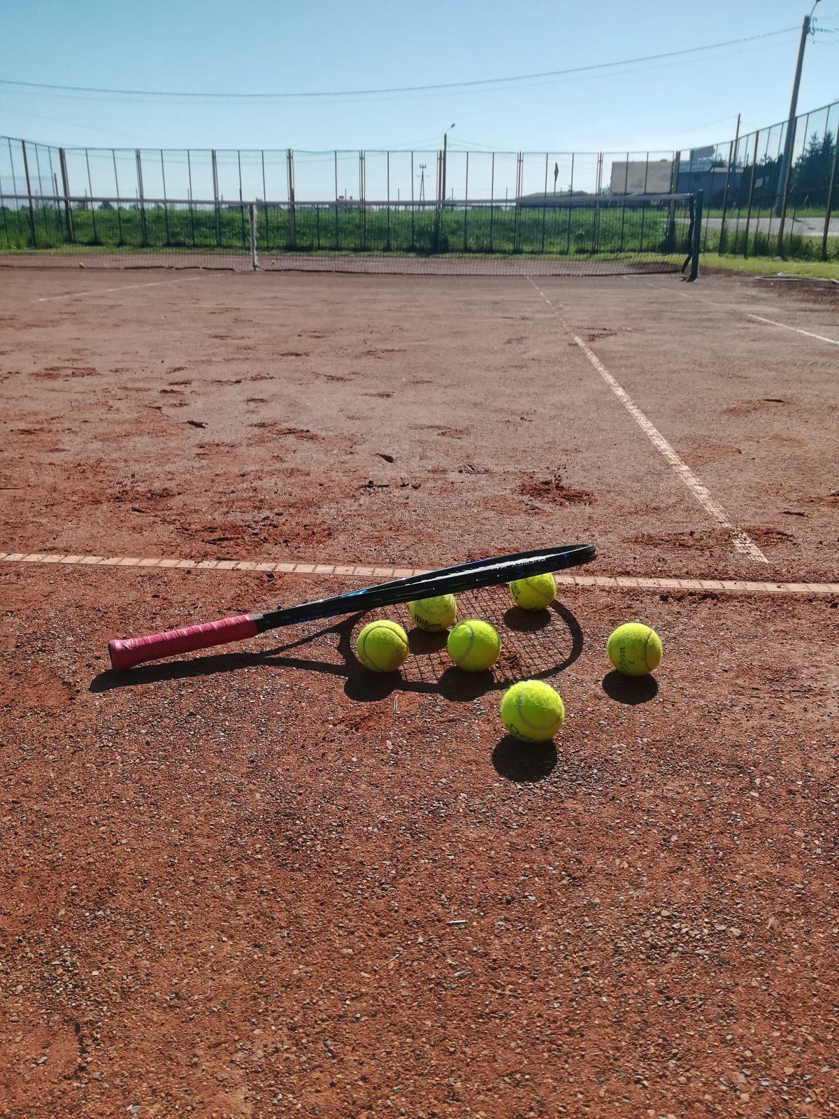 na korcie tenisowym lezy rakieta i kilka piłek